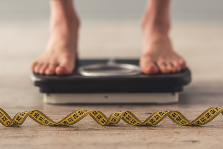 Photo pour Cropped image of woman feet standing on weigh scales, on gray background. A tape measure in the foreground - image libre de droit