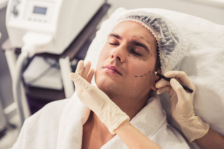 Photo pour Handsome man is sitting at the cosmetician while doctor in medical gloves is examining his face using a pencil - image libre de droit