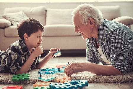 Photo pour Grandpa and grandson are playing with toys, looking at each other and smiling while resting together at home - image libre de droit
