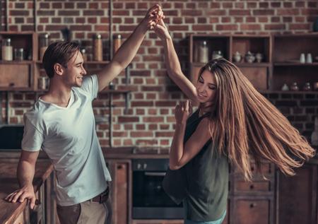 Foto de Young happy couple dancing at home in the kitchen - Imagen libre de derechos