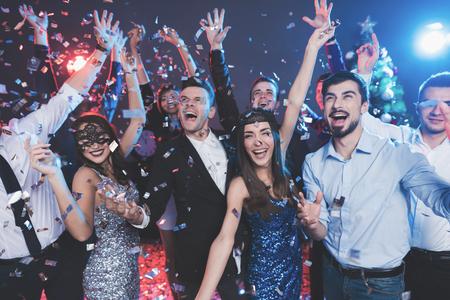 Foto de Young people have fun at a New Years party. Around them flies confetti. They are having fun. - Imagen libre de derechos
