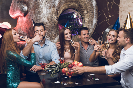 Foto de Young people are resting in a trendy nightclub. They clink glasses and drink champagne. - Imagen libre de derechos