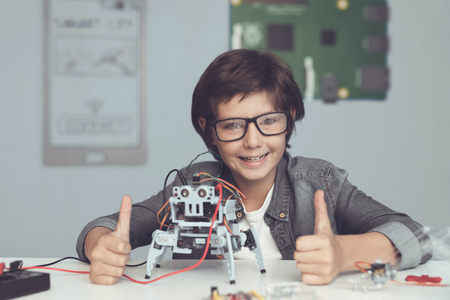 A small nerd in glasses is holding a robot. The boy looks very pleased and shows thumbs up