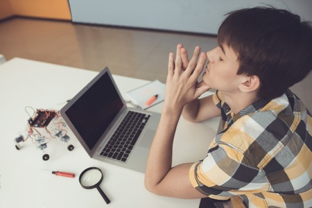 A teenager is sitting at a table in front of a laptop. Nearby is a robot which he assembled