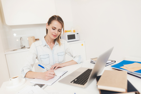 Photo for A woman works at home. She works on a laptop. - Royalty Free Image
