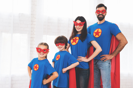 Foto de Young family in red and blue suits of superheroes. Their faces in masks and they are in raincoats. - Imagen libre de derechos