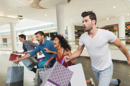 Foto de Sale in black Friday. The company of young people are engaged in shopping on a black Friday. - Imagen libre de derechos