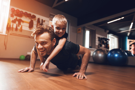 Foto de Father and son in the gym. Father and son spend time together and lead a healthy lifestyle. Man and boy are working out. Father and son are doing exercise. - Imagen libre de derechos
