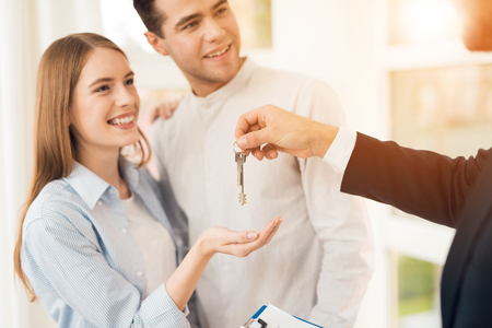 Photo pour Young couple in a meeting with a realtor. A guy and a girl make a contract with a realtor about buying a property. The realtor gives the couple a key to the new housing. - image libre de droit