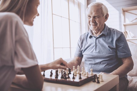 Photo pour Beautiful young girl-volunteer and handsome old man are playing chess and smiling - image libre de droit