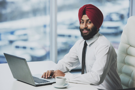 Photo pour Young indian bearded businessman working behind laptop in modern office. Business people. - image libre de droit