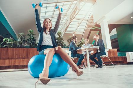 Foto de Female worker exercising on fitness ball in office. - Imagen libre de derechos