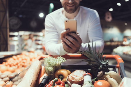 Foto für Close up. Man Using Cell Phone near Shopping Trolley. Father with Shopping Trolley. Shopping Cart with Food. Consumerism Concept. Man in Shirt. Shopping in Supermarket. Digital Device. - Lizenzfreies Bild