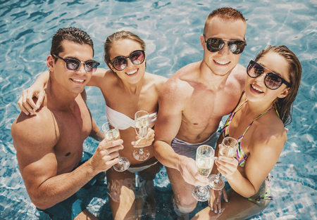 Beautiful Young People Having Fun in Swimming Pool and Drinking Wine. Leisure in Summer. Vacation in Summer. Recreation Concepts. Boyfriend and Girlfriend. Vacation for Couple. People in Swimsuit.