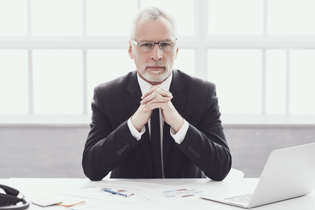 Photo pour Businessman at Work in Office. Corporate Lifestyle. Professional Mature Bearded Worker Sitting at Desk next to Laptop. Successful Confident Businessman wearing Suit and Glasses at Work. - image libre de droit
