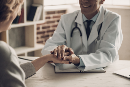 Close-up of Smiling Doctor Holding Patients Hand. Confident Medical Worker Sitting at Table in Cabinet and Making Conversation about Diagnosis with Hopefull Expression. Medical Issue Concept