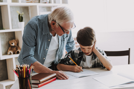 Photo pour Grandson Doing School Homework with Old Man Home. Family Relationship Between Grandfather and Grandson. Grandpa Teaching, Male Grandchild, Learning Concept. Relations and People Concept. - image libre de droit