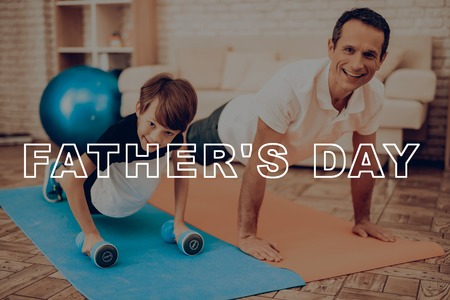 Father And Son Are Exercising With Fitness Ball. Healthy Lifestyle. Active Holiday. Exercises Clothes. Getting Better. Working Out At Home. Sports Equipment. Repeating Practice. Body Shaping.