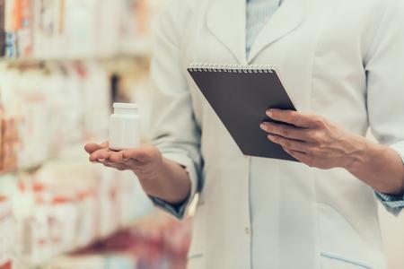 Closeup Pharmacist holds Pills Bottle and Notebook. Female Farmacist Wearing White Coat Holding Bottle of Pills and Notebook next to Shelves with Drugs in Pharmacy Store. Pharmacist in Drugstore