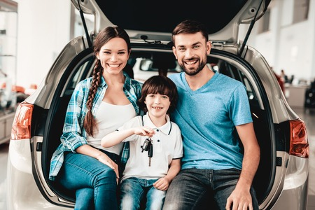 Photo pour Family Are Sitting In The Trunk Of A New Car. Smiling Customers. Buying In A Showroom. Automobile Salon. Happy Together. Successful Choice. Good Mood. Great Trade. Auto Rewiew. Make A Decision. - image libre de droit