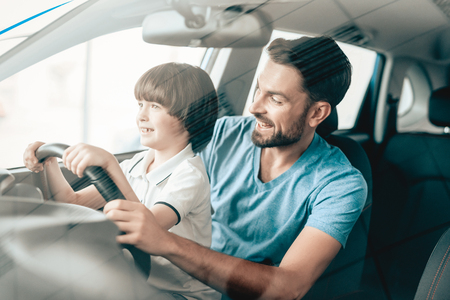 Photo pour Man With Kid Are Sitting At The Wheel Of New Vehicle. Smiling Family. Car Buying In A Showroom. Automobile Salon. Cheerful Driver. Happy Together. Father And Son. Good Mood. Great Trade. - image libre de droit