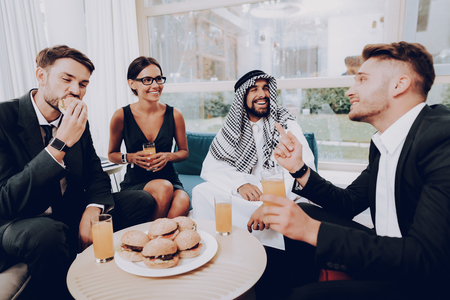 Photo pour Arabian Businessman Is Having A Dinner With Partners. Money Investment. Talking With Managers. Partnership Agreement. Disdash And Keffiyeh Wearing. Eating A Burgers. Business Discussion. - image libre de droit