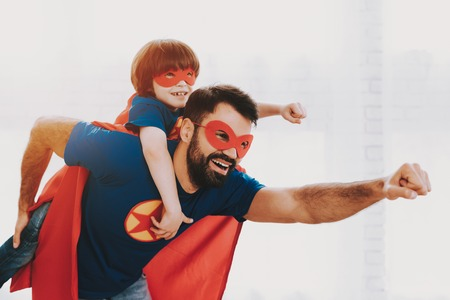 Foto de Father And Son. Red And Blue Superhero Suits. Masks And Raincoats. Posing In A Bright Room. Young Happy Family Holiday Concept. Resting Together. Save The World. Get Ready. Strong And Powerful. - Imagen libre de derechos