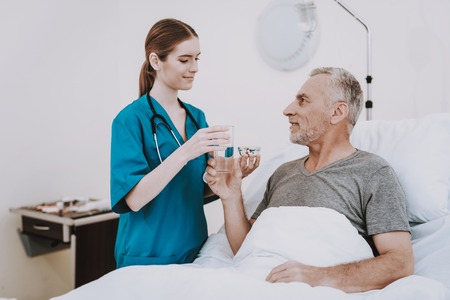 Therapy For Aged Man. People in Clinic. Professional Young Nurse. Interior in Hospital. White Room with Patient and Nurse. Rehab in Clinic. Stethoscope Help Patient in Clinic. Happy Patient and Nurse.