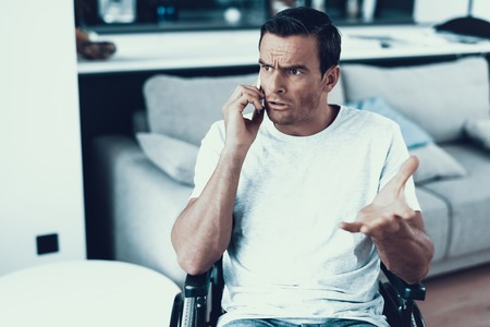 Disabled Person Has Serious Phone Conversation. Closeup Portrait of Caucasian Brown-haired Man Sits Indoors in Wheelchair Communicates Via Smartphone Wearing White T-Shirt Showing Sad Face Expression