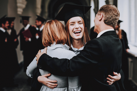 Photo pour Relations. Diploma. Parents. Congratulations. Student. Finish Studies. University. Graduates. Happy. Good Mood. Have Fun. Architecture. Happiness. Standing. Corridor. Mother. Father. Daughter. - image libre de droit
