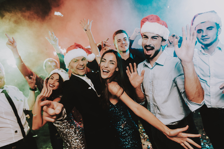 Foto de People in Santa Claus Cap Celebrating New Year. Happy New Year. People Have Fun. Indoor Party. Celebrating of New Year. Young Woman in Dress. Young Man in Suit. Happy People. Red Cap. - Imagen libre de derechos