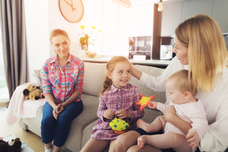 Photo pour Mother with Lovely Kids Sits on Couch near Nanny. Happy Businesswoman Holds Baby on Hands and Caresses Daughters Head in Bright Living Room. Smiling Nanny Sitting on Comfortable Sofa - image libre de droit