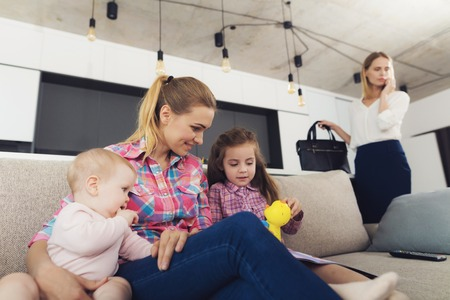 Photo pour Babysitter Looks After Kids while Mom Telephones. Young Nanny Wearing Casual Clothes Sitting on Couch and Playing with Kids. Businesswoman Talking Phone in Bright Living Room - image libre de droit