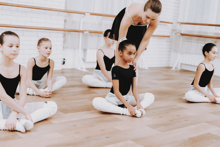 Photo for Ballet Training of Girls on Floor with Teacher. - Royalty Free Image