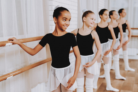 Photo pour Ballet Training of Group of Young Girls Indoors. Classical Ballet. Girl in Balerina Tutu. Training Indoor. Cute Dancers. Performance in Hall. Dancing Practice. Girls in White Dresses. - image libre de droit