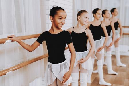 Foto de Ballet Training of Group of Young Girls Indoors. Classical Ballet. Girl in Balerina Tutu. Training Indoor. Cute Dancers. Performance in Hall. Dancing Practice. Girls in White Dresses. - Imagen libre de derechos