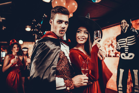 Foto de Young Happy Couple in Costumes at Halloween Party. Handsome Man and Beautiful Woman Drinking Champagne at Halloween Party in Nightclub. Friends having Fun. Celebration of Halloween - Imagen libre de derechos