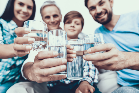 Foto de Smiling Family Drinking Water in Glasses at Home. Father and Son. Smiling People. Parenthood Concept. Family at Home. Happy Family. Glass of Water. Young Woman. Family in Dining Room. - Imagen libre de derechos
