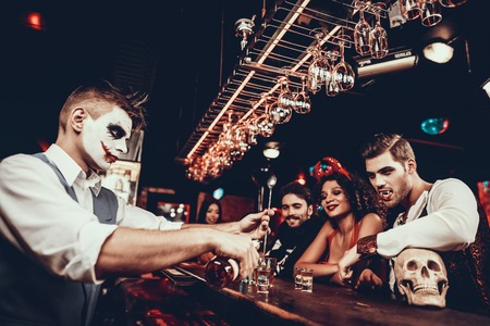 Foto de Bartender in Halloween Costume Making Cocktail. Group of Young People Wearing Costumes standing nex to Bar counter and waiting for Cocktails at Halloween Party in Nightclub. Celebration of Halloween - Imagen libre de derechos