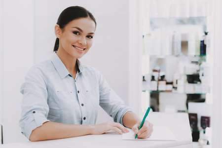 Photo pour Woman Receptionist. Receptionist in Workplace. Workplace in Beauty Salon. White Interior. White Reception Desk. Beauty Consept. Smiling Salon Employee. Customer Registration. Consept Beauty Salon. - image libre de droit