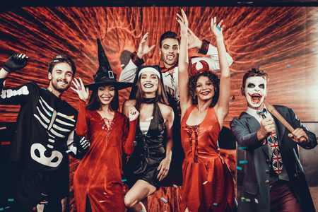 Photo for Portrait of Young Smiling People in Scary Costumes. Group of Young Happy Friends Wearing Halloween Costumes having Fun Together and posing for Group photo in Nightclub. Halloween Celebration - Royalty Free Image