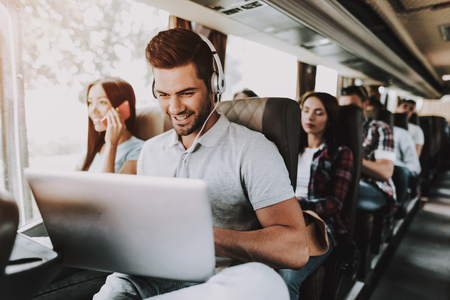 Foto de Smiling Man in Headphones Using Laptop in Tour Bus. Young Handsome Man Sitting on Passenger Seat of Tourist Bus and Typing on Laptop. Traveling and Tourism Concept. Happy Travelers on Trip - Imagen libre de derechos