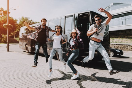 Photo pour Excited Young People Jumping in front of Tour Bus. Group of Smiling Friends with Backpacks Jumping Together and Laughing. Traveling, Tourism and People Concept. Happy Travelers on Summer Vacation - image libre de droit