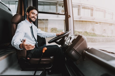 Photo pour Smiling Man Driving Tour Bus. Professional Driver. Young Happy Man wearing White Shirt and Black Tie Sitting on Driver Seat. Attractive Confident Man at Work. Traveling and Tourism Concept - image libre de droit