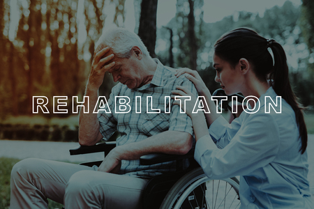 Doctor Calms Dejected Old Man. Old Man Crying. Disabled in Wheelchair. Good Medicine in Nursing Home. Old Man in Sunny Park. Man Sit in Wheelchair. Outdoor Rehabilitation. Old Man Retirement.