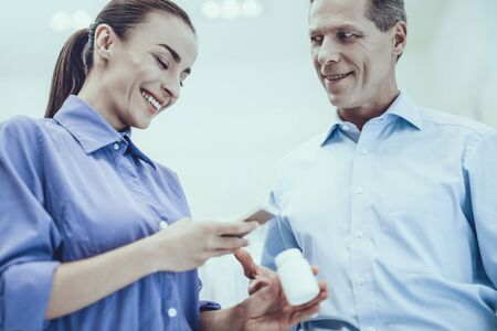 Photo pour Man and Woman Choose a Medicaments. Man Looking at Smiling Woman. Woman Holding a Bottle with Pills. Woman Watching Information About a Medicament on Mobile Phone. People Located in Pharmacy. - image libre de droit