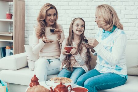 Photo pour Family Celebrating Birthday and Sitting at Home. Cake on Table. Happy Family. Mother with Daughter. Smiling Women at Home. Smiling Grandmother. Celebration Concept. Cup of Tea. Cup in Hand. - image libre de droit