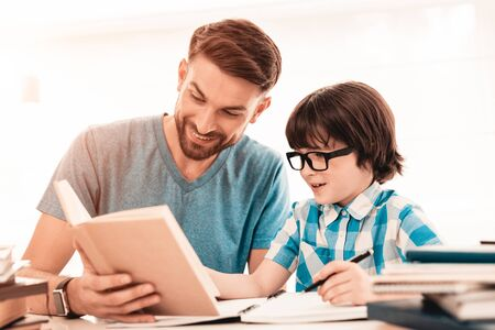 Photo pour Little Boy in Glasses Doing Homework with Father. Education at Home. White Table in Room. Sitting Boy. Young Father. Lesson at Home. Education Concept. - image libre de droit
