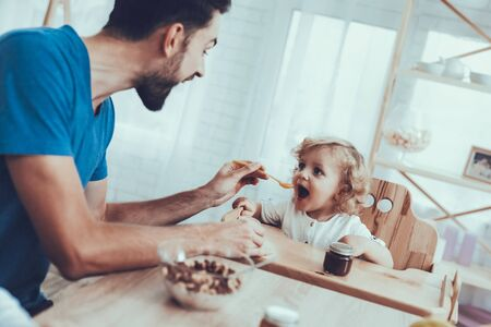 Man Spends Time with His Son. Father of Boy is Engaged in Raising Child. Father is Feeding His Son from Spoon. Man is Smiling. People is Sitting on Chairs at Table. People Located on Kitchen.