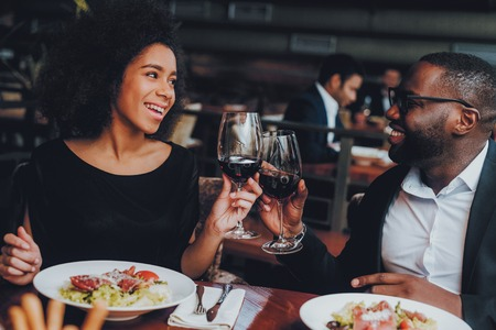 Foto de African American Couple Dating in Restaurant. Romantic Couple in Love Dating. Cheerful Man and Woman with Menu in a Restaurant Making Order. Romantic Concept. Cheers Classes Red Wine. - Imagen libre de derechos